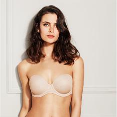 A woman wearing a beige strapless bra. Shop strapless.