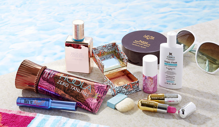 An assortment of bronzers, SPF skincare, lipsticks and more on the edge of a swimming pool.