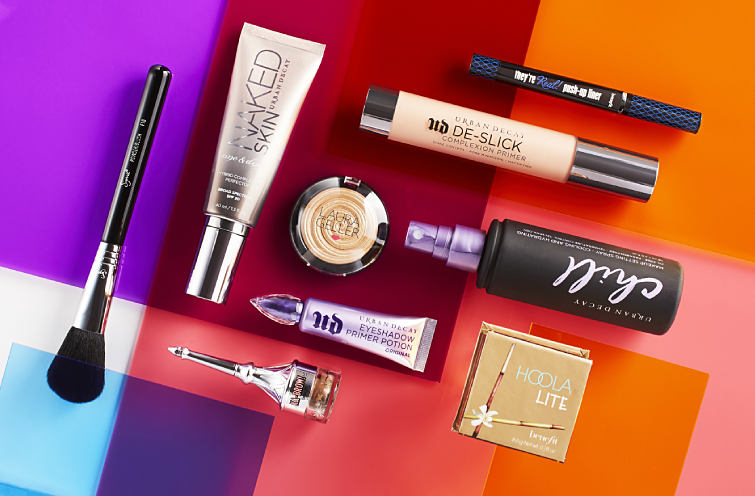 An assortment of contemporary beauty products including primer and bronzer on a brightly colored background.