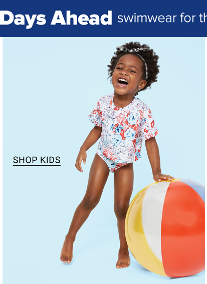 A toddler girl in a printed swimsuit. Shop kids.