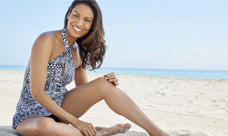 A woman sitting on the beach wearing a black and white swimsuit.