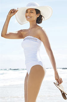 A woman wearing a white wide brimmed sun hat & a white 1 piece swimsuit. Shop 1 piece.