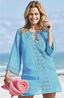 A woman wearing a light blue long sleeved beach cover up with lace detail. Shop cover ups.