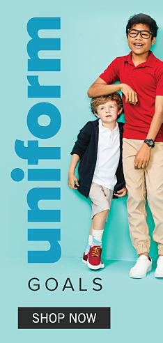 A boy wearing a navy cardigan over a white polo, beige shorts & red sneakers standing next to a boy wearing glasses, a red polo, beige pants & white sneakers. Uniform Goals. Shop uniforms.