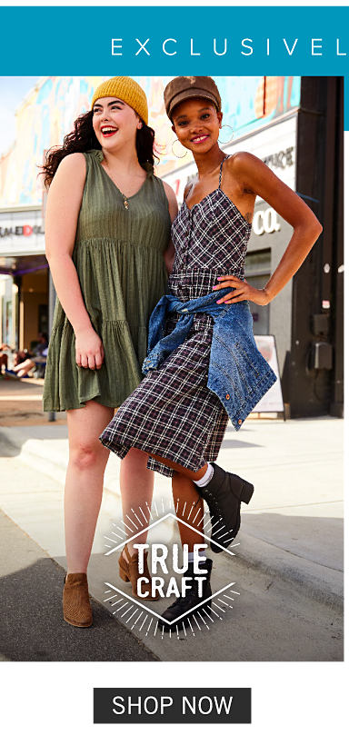 A young woman wearing a gold knit hat & an olive sleeveless dress standing next to a young woman wearing a brown hat & a blue & white plaid sleeveless dress with a denim jacket tied around her waist. Shop True Craft.