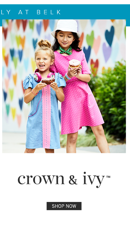 A girl wearing a light blue short sleeved dress with pink trim standing next to a girl wearing a white hat & a fuschsia short sleeved dress with white dots. Shop Crown & Ivy.