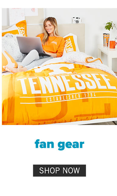 A young woman wearing an orange long sleeved top with a white left chest University of Tennessee logo & gray pants lounging on a bed made with an orange & white University of Tennessee logo comforter & matching pillows. Fan Gear. Shop now.