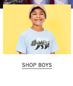 A boy wearing a beige knit hat & a white T shirt with a multi colored bear front graphic. Shop boys.