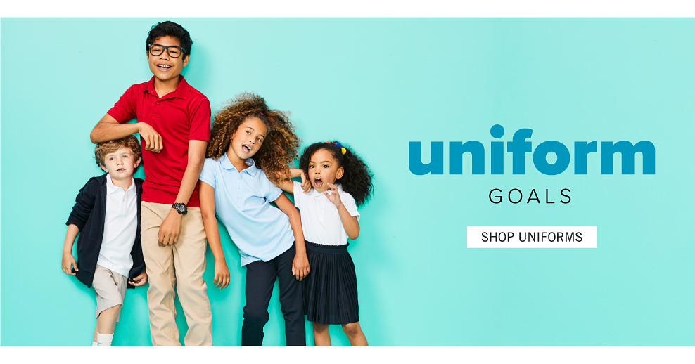 A boy wearing a navy cardigan over a white polo, beige shorts & red sneakers standing next to a boy wearing glasses, a red polo, beige pants & white sneakers, a girl wearing a light blue polo & navy pants & a girl wearing a white polo & navy skirt. Uniform Goals. Shop uniforms.