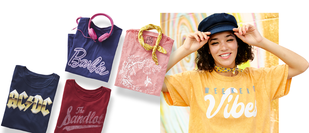An assortment of graphic tees in a variety of colors, prints & styles. A young woman wearing a navy fisherman's hat, a yellow T shirt with a white & gray Weekend Vibes front graphic & denim shorts. Fresh Prints. Graphic Tees. Shop now.