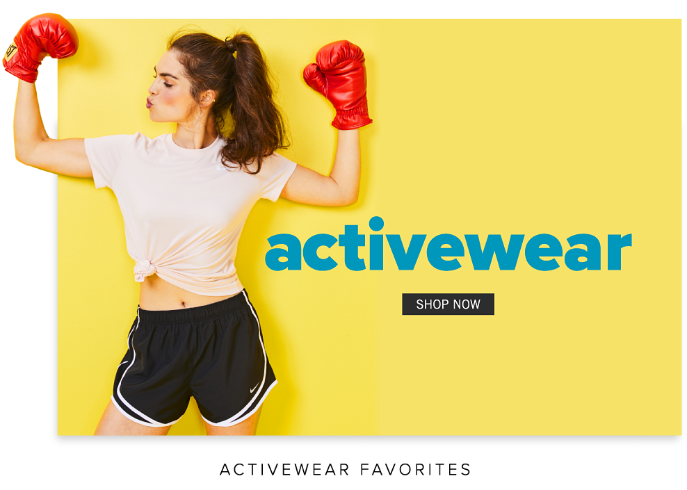 A youing woman wearing red boxing gloves, a white T shirt & navy shorts with white trim. Activewear. Shop now.