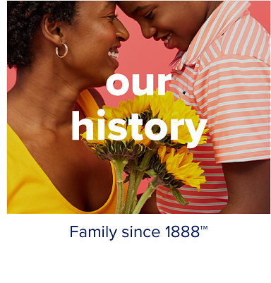 A mother in a yellow shirt touches foreheads with her son, who wears an orange and white striped button up. Our history. Family since 1888.