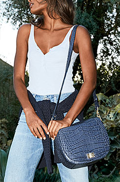 A woman wearing a white tank top and jeans and carrying a blue leather handbag.