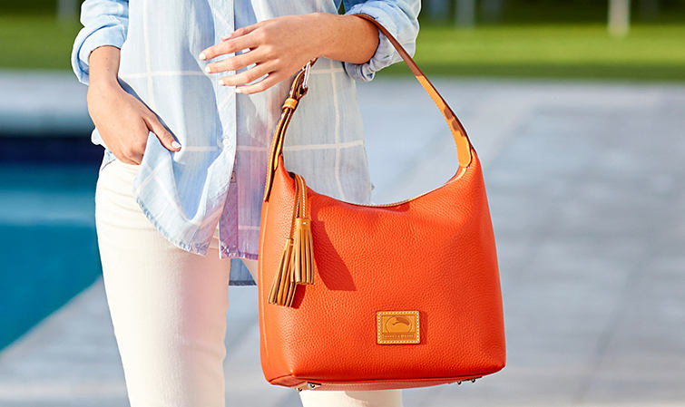 A woman standing by a pool wearing a blue top with white pants carrying a bright orange Dooney & Bourke handbag.