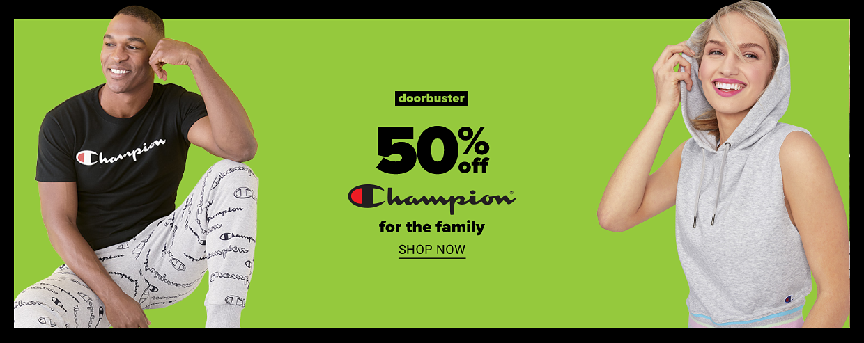 Man in black Champion graphic tee shirt and light gray sweatpants with printed logos throughout. A woman in a light gray sleeveless hoodie with drawstrings. Doorbuster. 50% off Champion for the family. Shop now.