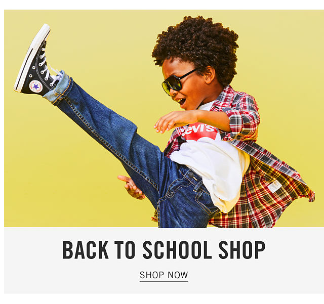 A boy wearing sunglasses, a multi colored plaid long sleeved button front shirt over a white T shirt with a red Levi's front logo, blue jeans & black high top sneakers. Back to School Shop. Shop now.