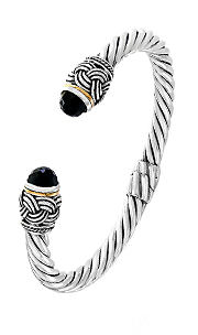 A silver bracelet with black and gold detail. Shop Bracelets.
