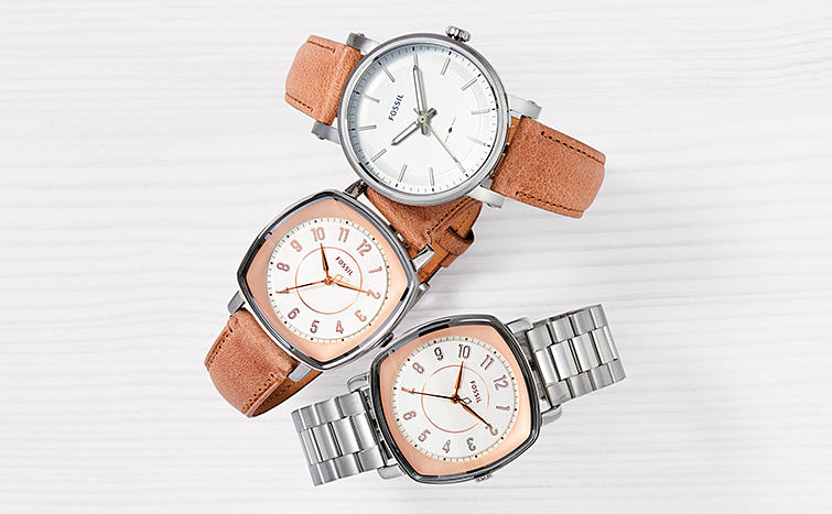 Three different Fossil watches, two with leather brands and one with a silver band.