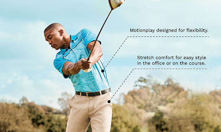 A man playing golf wearing a blue polo and khaki pants.