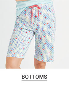 A woman in knee length, printed sleep shorts. Shop bottoms.