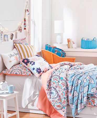 A bed made with a couple of colorful print quilts and a colorful novelty throw pillows.
