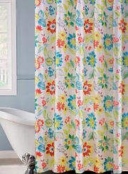 A colorful floral print shower curtain hanging over a clawfoot bathtub. Shop shower curtains.