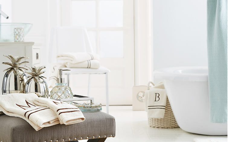 An assortment of monogrammed towels on a gray stool in front of a collection of glass and mirrrored pineapple-themed bath accessories. Shop bath.