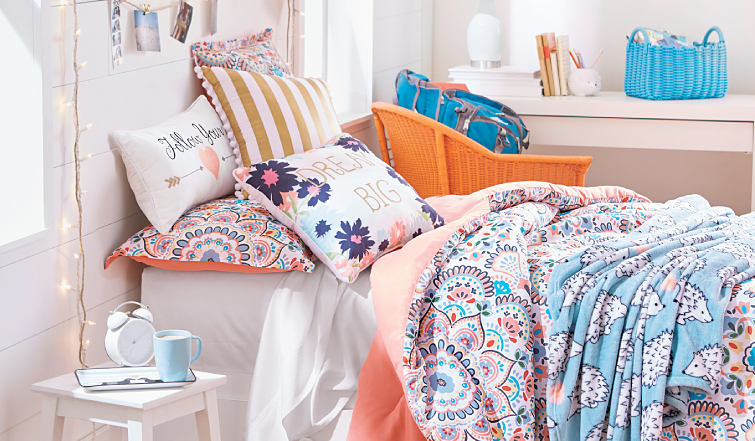 A bed made with a couple of colorful print quilts and a variety of novelty pillows.