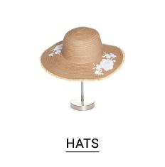 A beige sun hat with white flower detail. Shop hats.