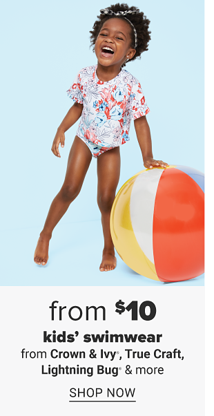 A little girl in a short sleeve printed swim top and bottoms standing next to a beach ball. From $10 kids' swimwear from Crown and Ivy, True Craft, Lightning Bug and moe. Shop now.