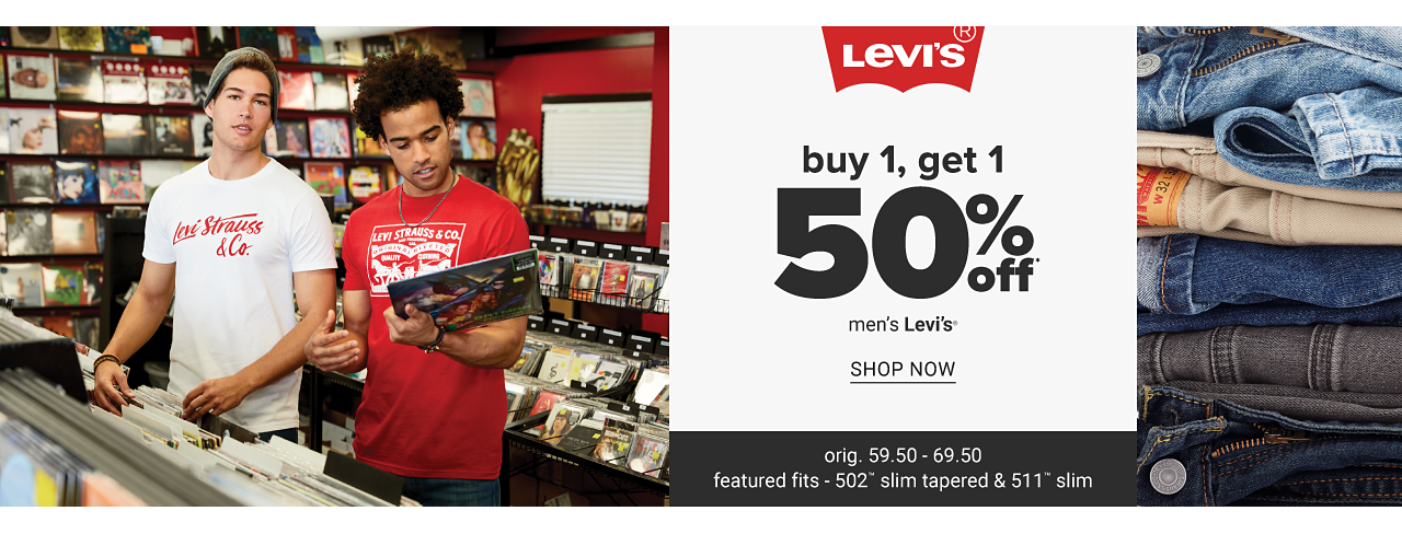 A young man wearing a gray knit hat & a white T shirt with a red Levi's front graphic & blue jeans standing next to a young man wearing a red T shirt with a white Levi's front graphic & blue jeans. An assortment of jeans in a variety of colors & styles. Buy 1, Get 1 50% off men's Levi's. Shop now.