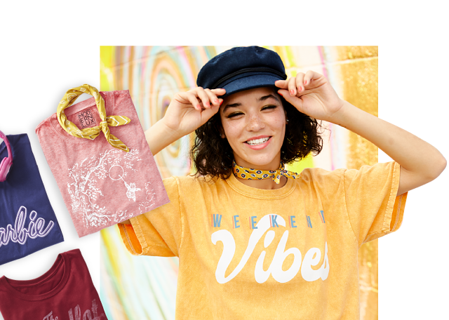 An assortment of graphic tees in a variety of colors, prints & styles. A young woman wearing a navy fisherman's hat, a yellow T shirt with a white & gray Weekend Vibes front graphic & denim shorts.