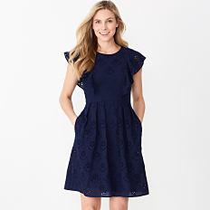 A woman wearing a navy short sleeved dress. Shop dresses.