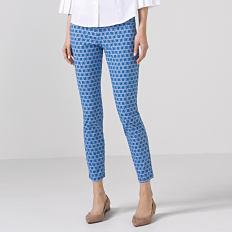 A woman wearing a white blouse, blue & white patterned print pants & beige flats. Shop pants.