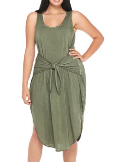 A young woman wearing an olive green sleeveless dress. Shop dresses.