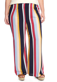 A young woman wearing a white short sleeved top & multi colored vertical striped pants. Shop pants.