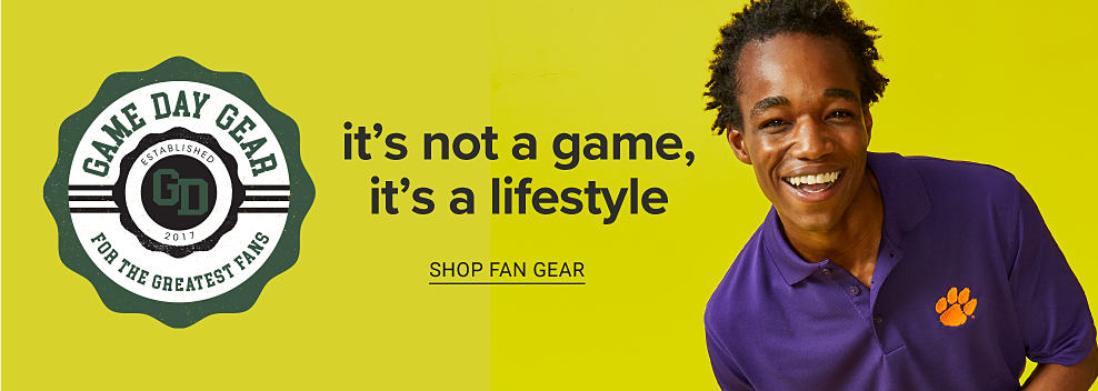 A young man wearing a team polo. Game day gear. For the greatest fans. It's not a game, it's a lifestyle. Shop fan gear.