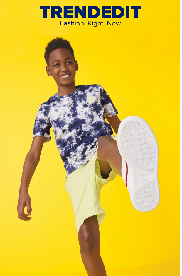 A boy in a blue and white tie dye shirt and yellow shorts holds his foot up as if in the middle of a step. Trend Edit. Fashion right now.