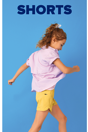 A girl wears a purple button up shirt with rolled up cuffs and yellow shorts. Shorts.