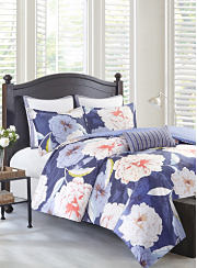 A bed made with a white, purple and violet floral print comforter, matching pillows and white sheets. Shop comforters.