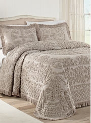 A bed made with a beige bedspread and matching pillows. Shop bedspreads.