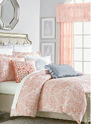 A bed made with a salmon and white patterned comforter, matching pillows and white sheets. Shop designer bedding.