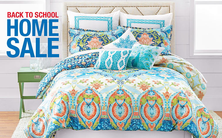 A bed made with a multi color patterned comforter and multi color patterned pillows.