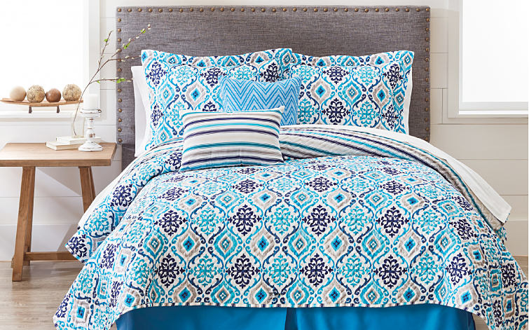 A bed made with a blue, navy, beige and white comforter and matching pillows.