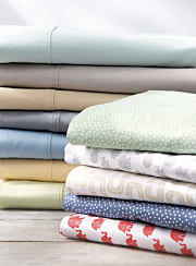 Two stacks of folded bed sheets in a variety of colors and patterns. Shop sheets.