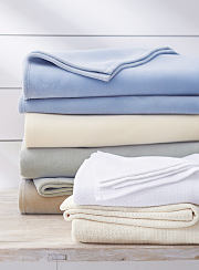Two stacks of blankets in a variety of colors. Shop blankets.