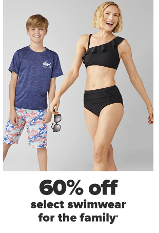 A little boy in a heathered blue shirt with a fish decal on the breast and blue, pink and white swim trunks. A woman in a black bikini set with a ruffle accent and holding a pair of sunglasses. 60% off select swimwear for the family.