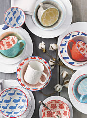 A wooden table set with white plates and multi color animal patterned mugs and bowls.