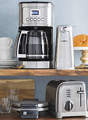 An assortment of small appliances surrounded by pastries, cups and saucers.