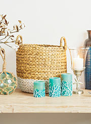 An assortment of ceramic vases, wicker baskets and candles, all boasting a seaside theme.